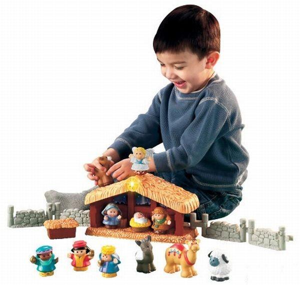 Jongetje speelt met kerstbeeldjes